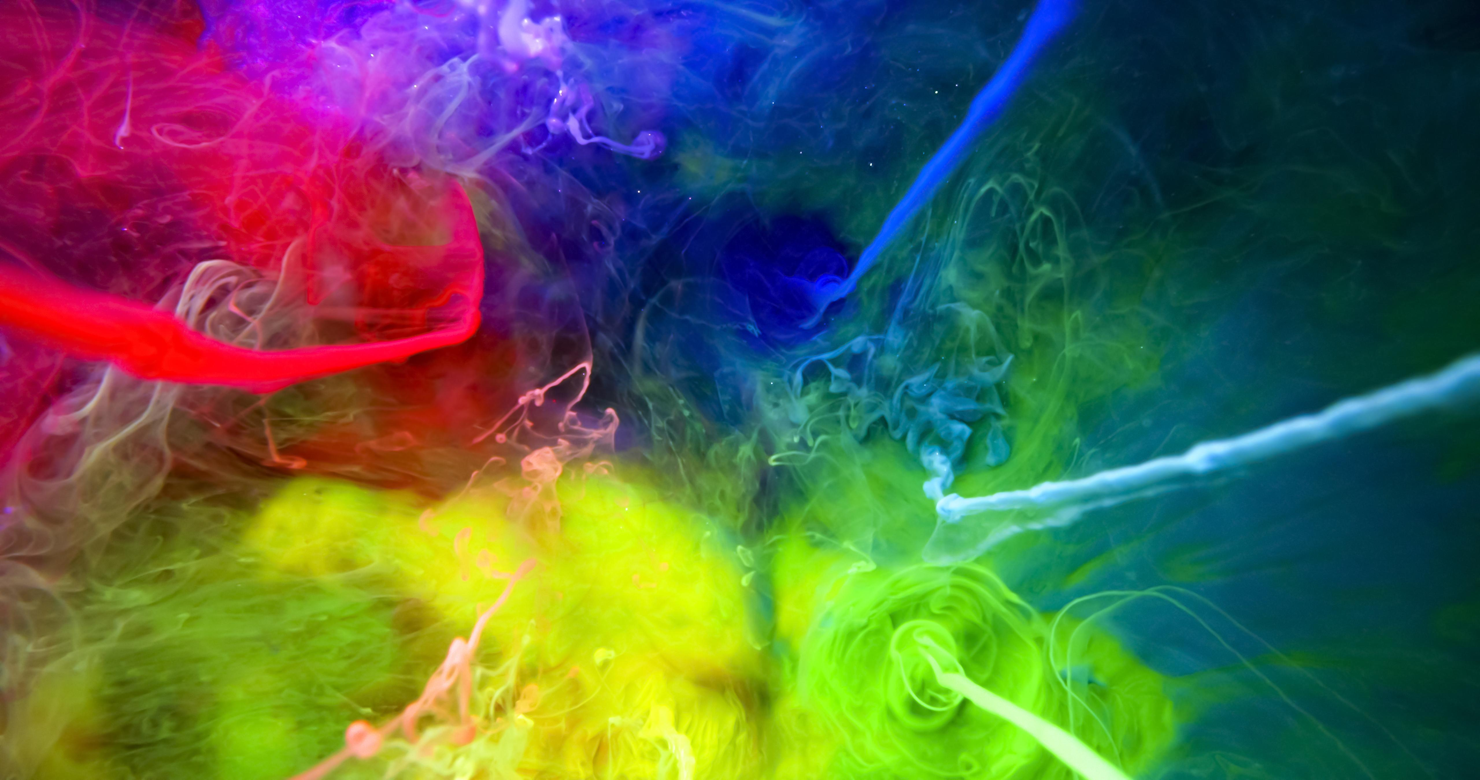 An abstract background with brightly coloured ink clouds